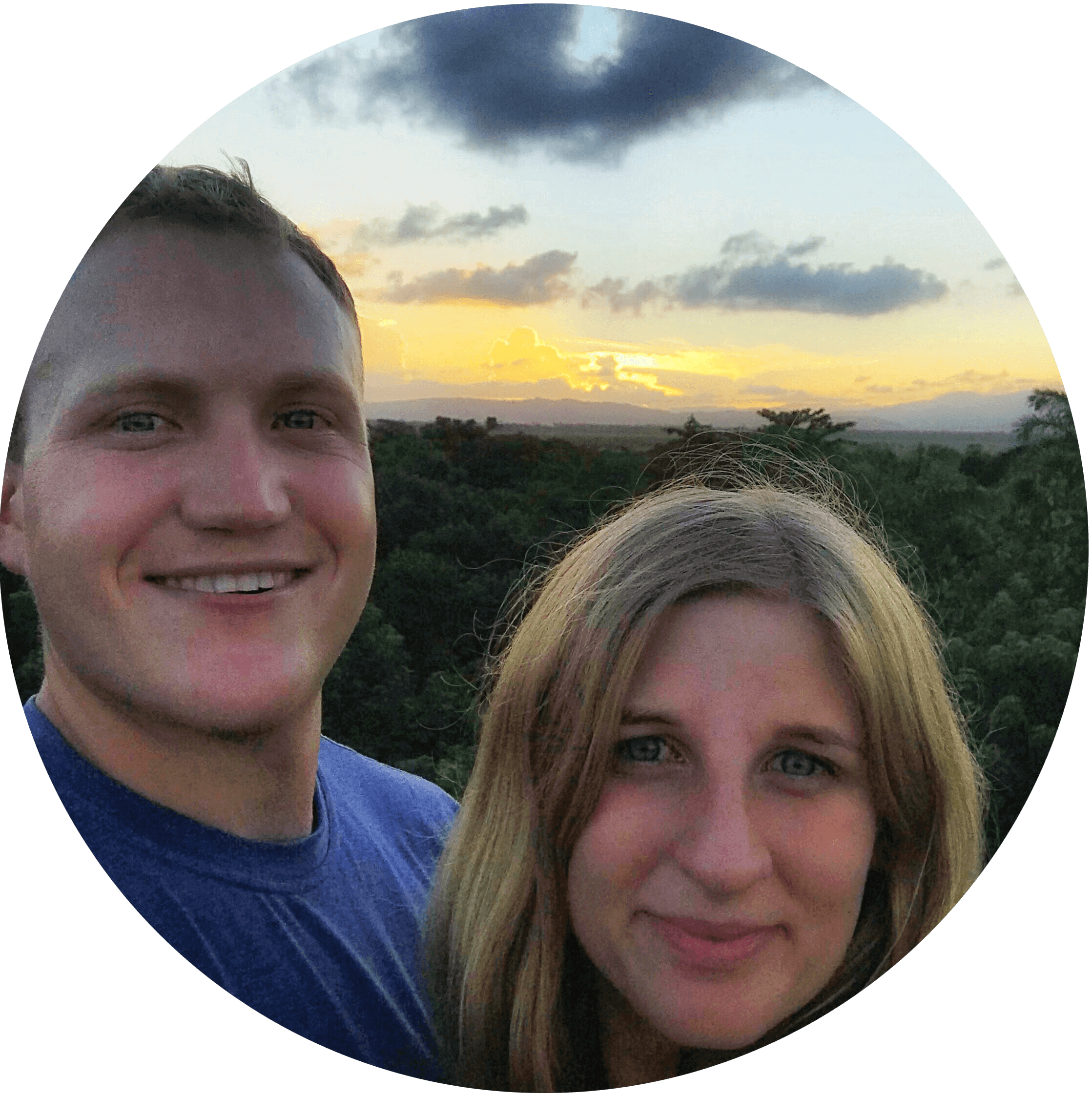 Nicholas Dumke and a female smiling in front of a sunset