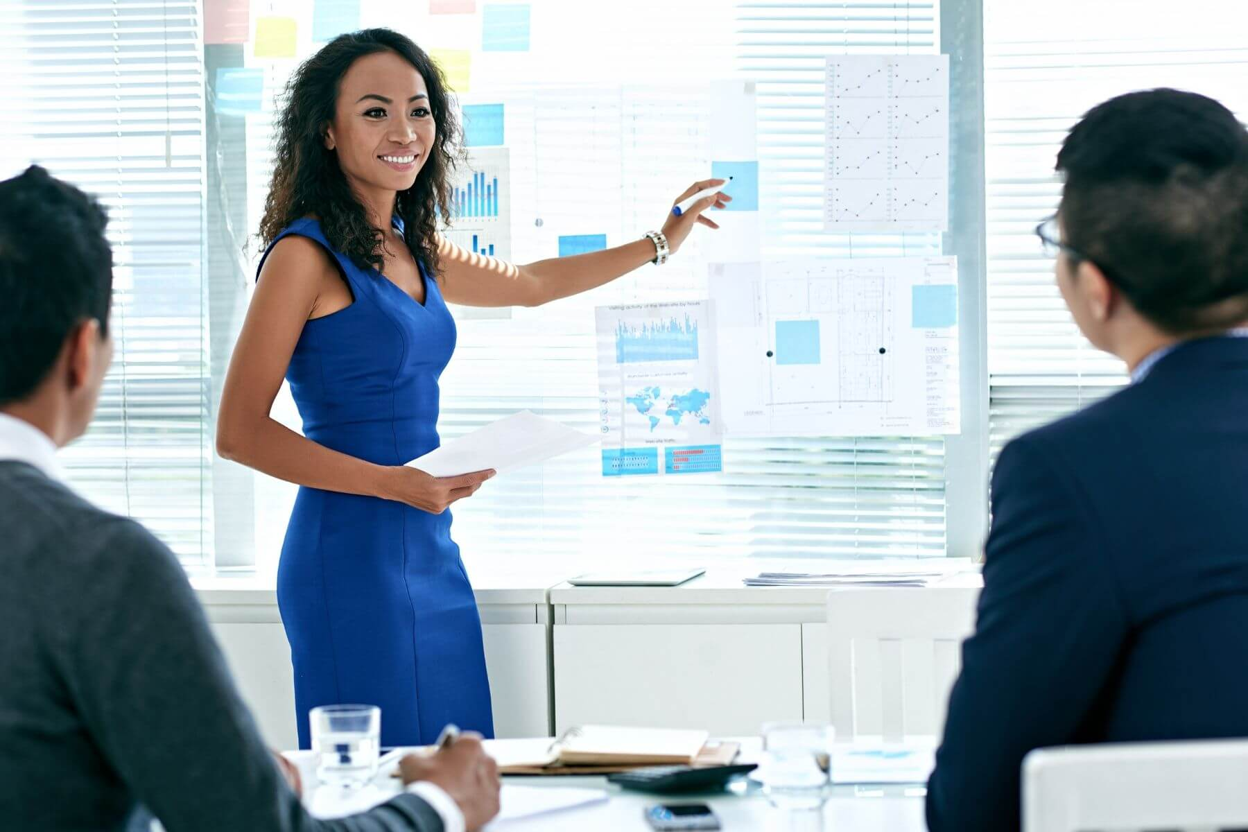 Female professional in blue dress smiling during as she presents in a corporate setting.