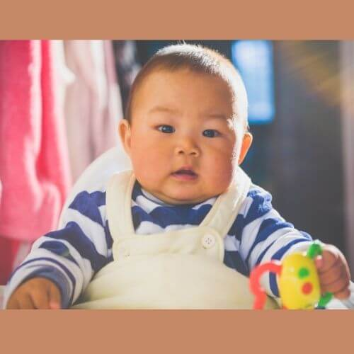 Infant boy in overalls with blue triped shirt grasping toy.jpg