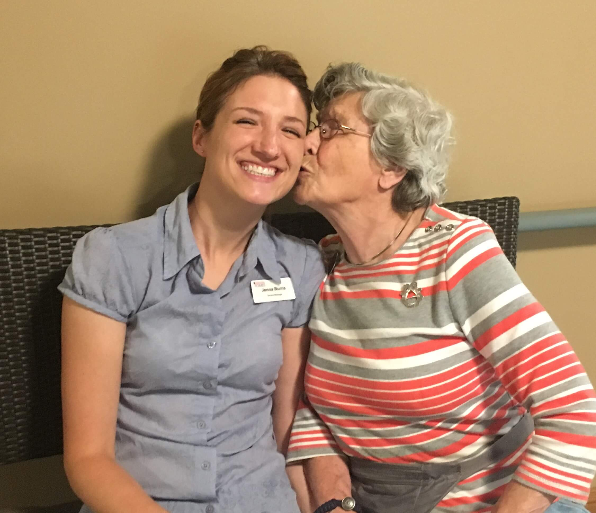 Jenna Kilawee smiling at the camera as a female resident in her assisted living facility sits next to her kissing her cheek.