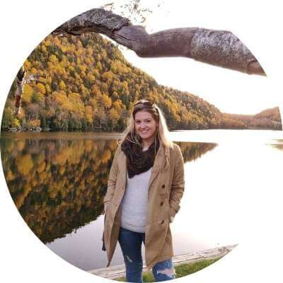 Molly Roush smiling standing in front of a lake and trees in the fall