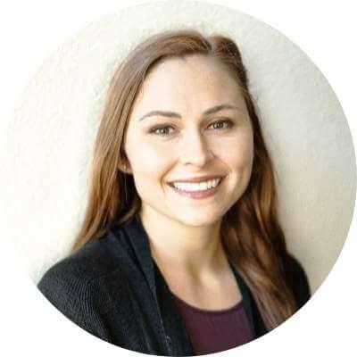 Sara Hanna smiling at the camera standing by wall