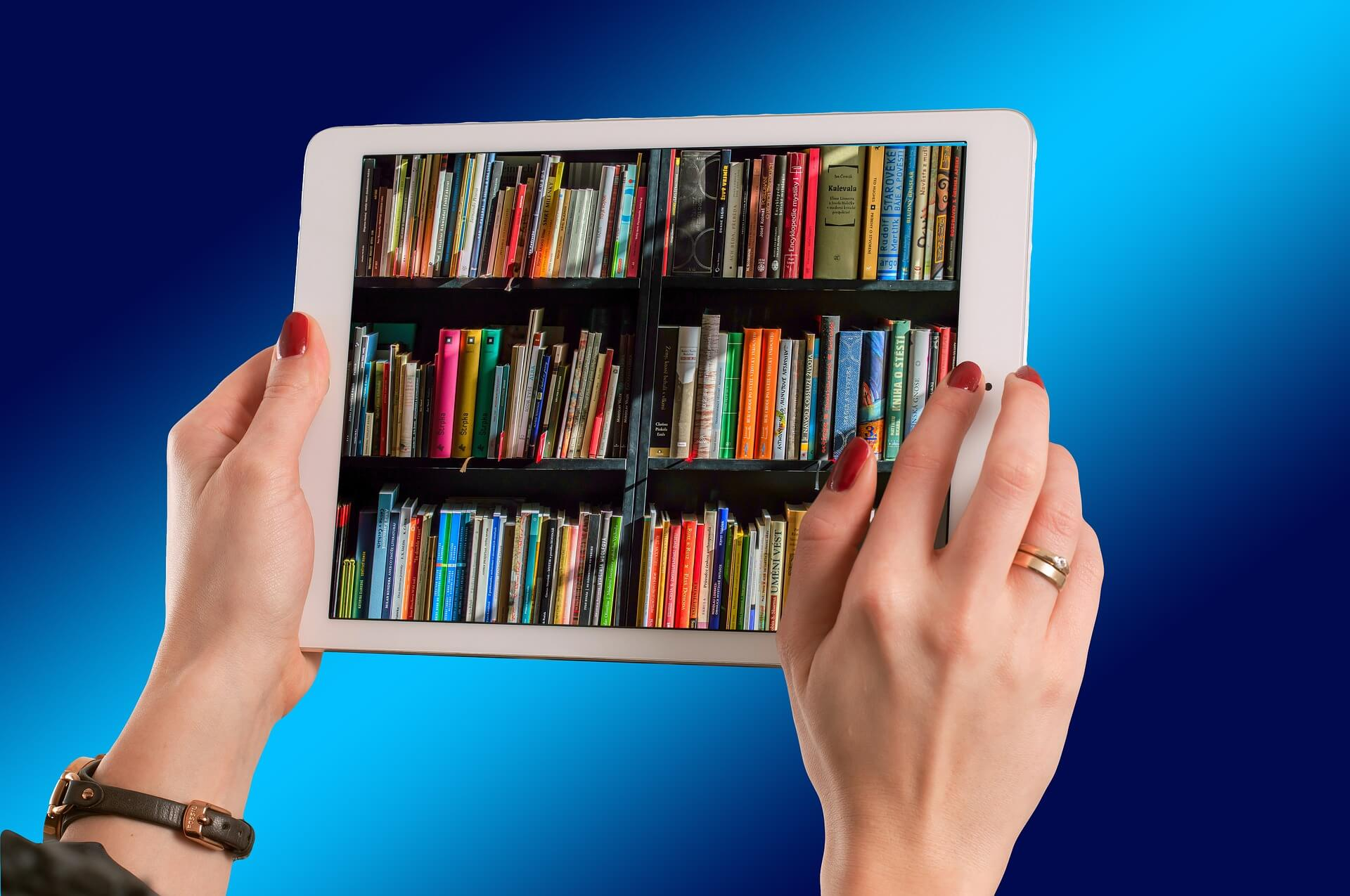 Female hands hold a tablet displaying a photo of library shelves filled with books.